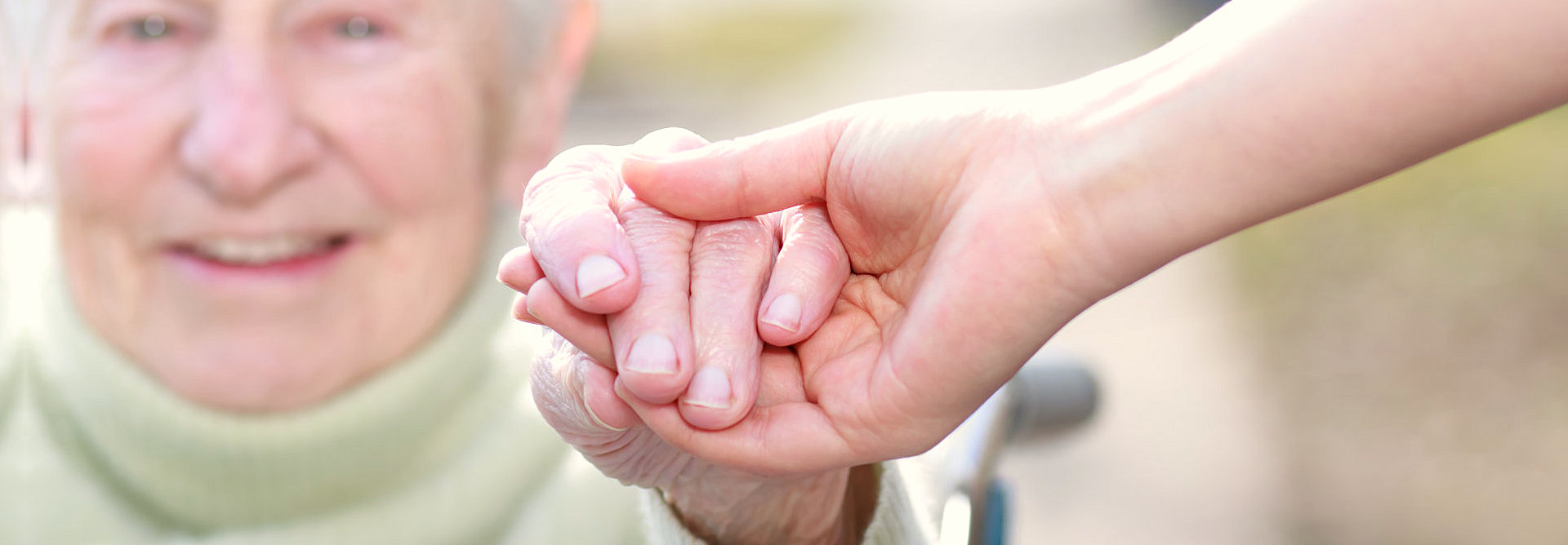 caregiver holding the hand of an elder
