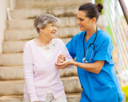 caregiver assisting patient in walking down the stairs
