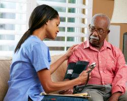 caregiver taking patients blood pressure
